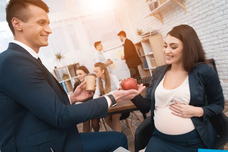 El hombre hermoso en traje da la manzana a la mujer embarazada joven en oficina Embarazo en el trabajo fotos de archivo libres de regalías