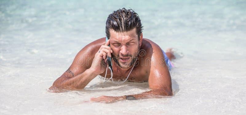 El hombre hermoso está poniendo en el agua azul del Océano Índico y está hablando por el teléfono fotos de archivo