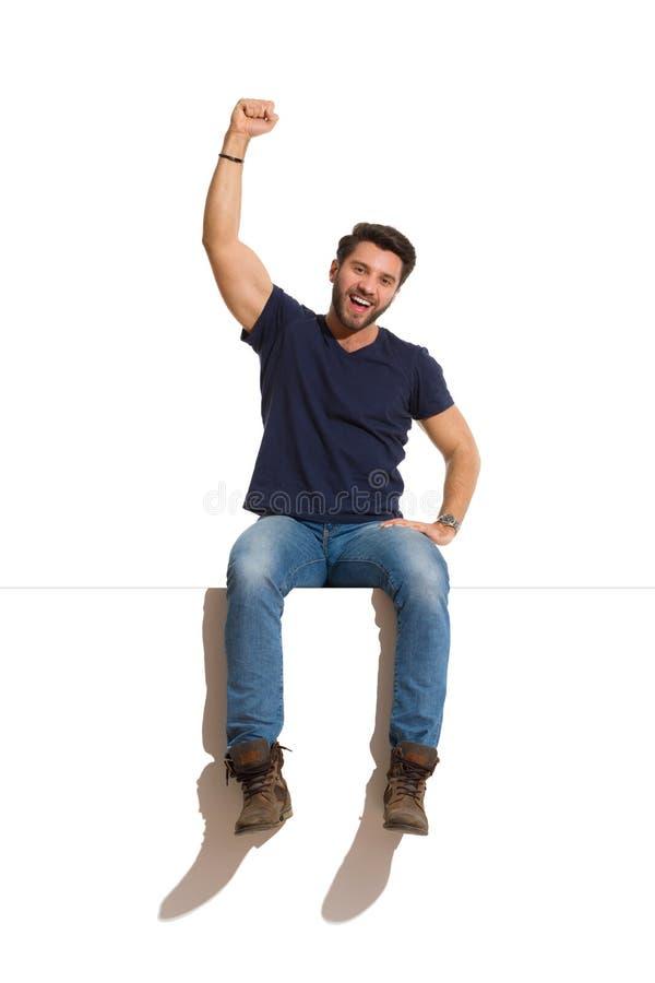 El hombre hermoso feliz de grito se está sentando en un top y un brazo de levantamiento foto de archivo
