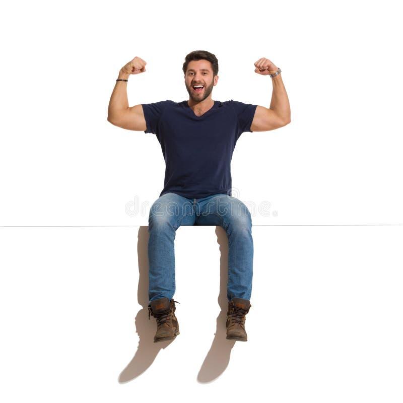 El hombre hermoso feliz de grito se está sentando en un top y doblar los músculos fotografía de archivo libre de regalías