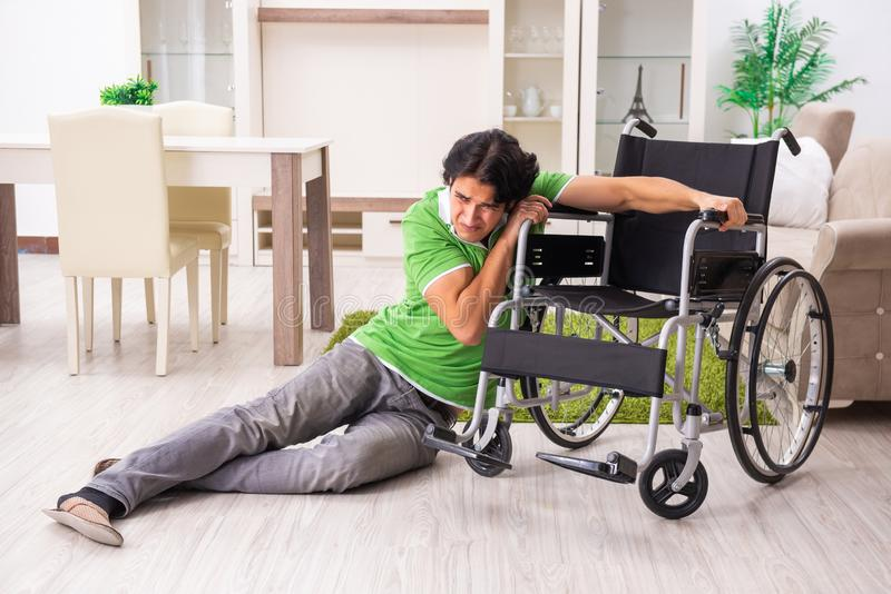 El hombre hermoso joven en silla de ruedas en casa fotos de archivo