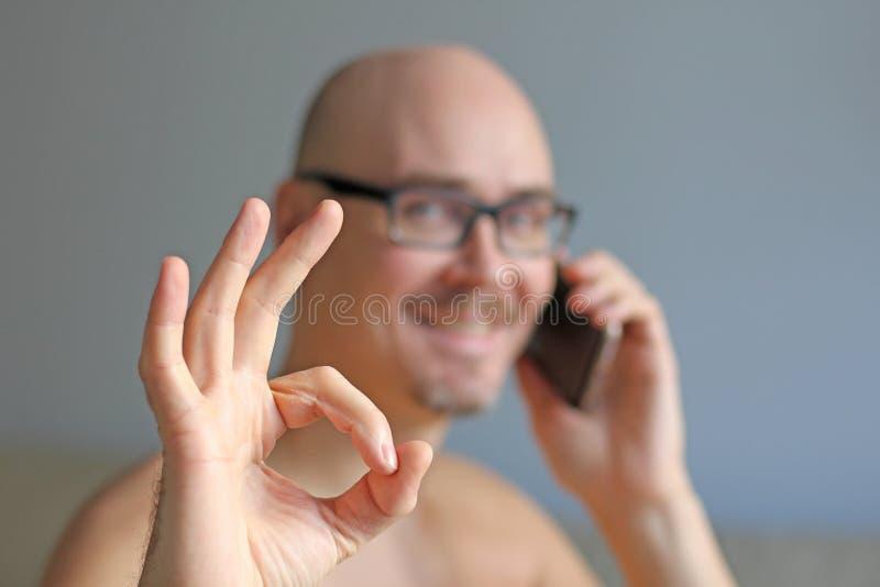 El hombre hermoso joven en vidrios negros está hablando en el teléfono Noticias positivas Retrato de un cierre del hombre para ar imagenes de archivo