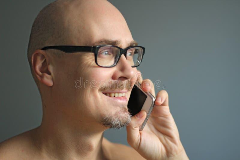 El hombre hermoso joven en vidrios negros está hablando en el teléfono, sonriendo Retrato del primer de un hombre Encargado, ofic imagen de archivo