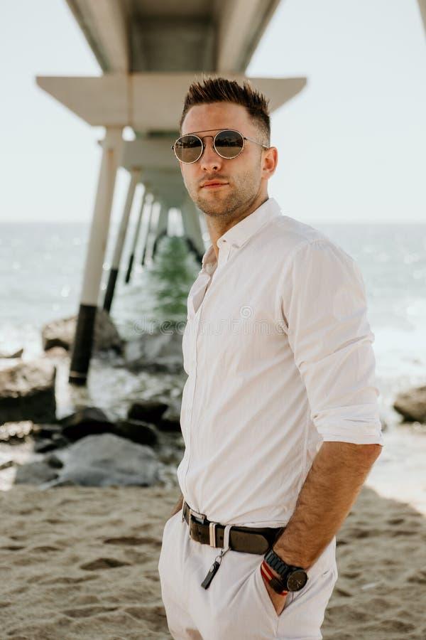 El hombre hermoso joven que camina en el mar, disfruta de la estación de verano Relaje al hombre joven caucásico que considera le imagenes de archivo