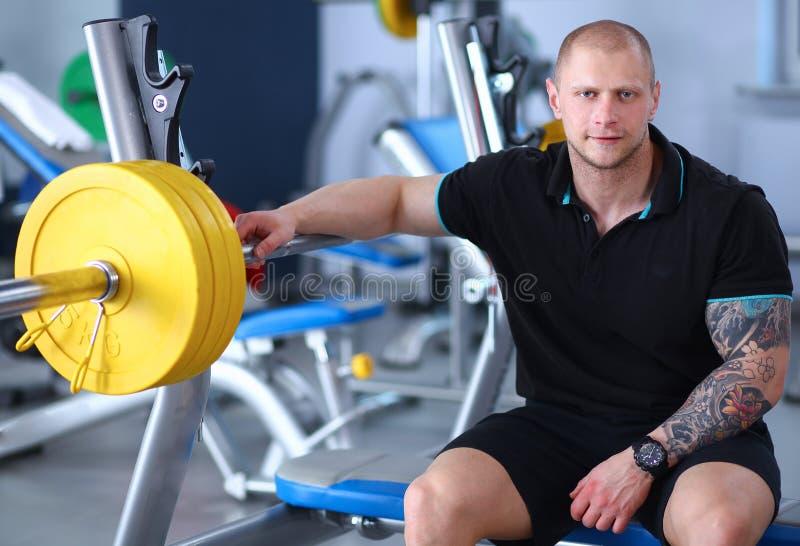 El hombre hermoso joven se sienta después de entrenamiento en el gimnasio fotos de archivo