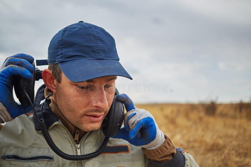 El hombre hermoso saca los auriculares en el aire abierto imagen de archivo