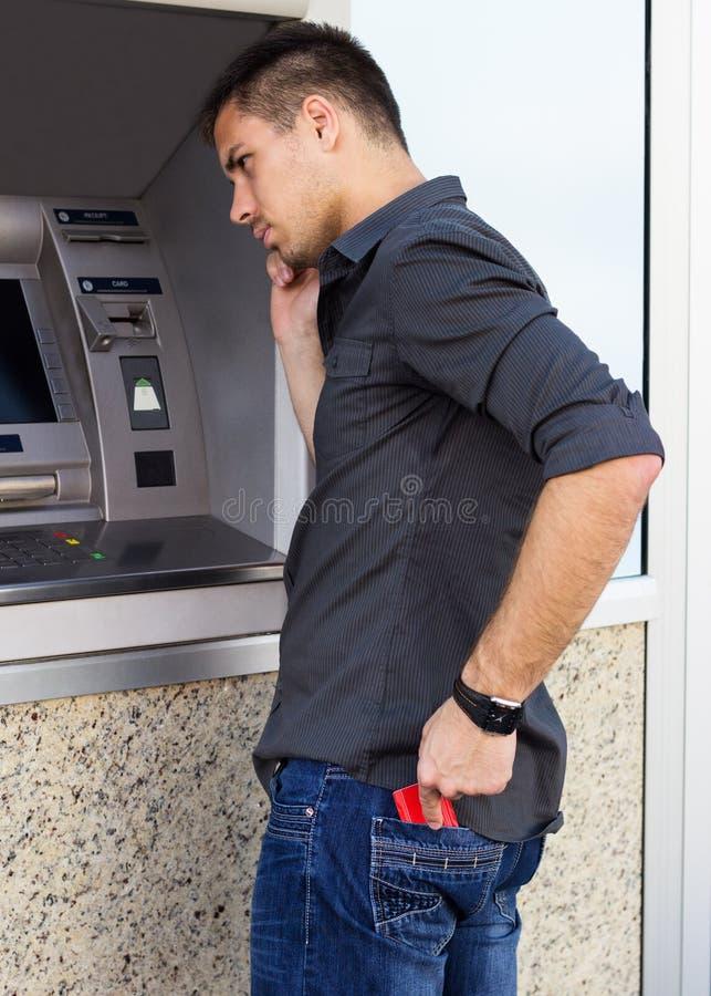 El hombre hermoso saca una tarjeta de crédito de su bolsillo imagenes de archivo