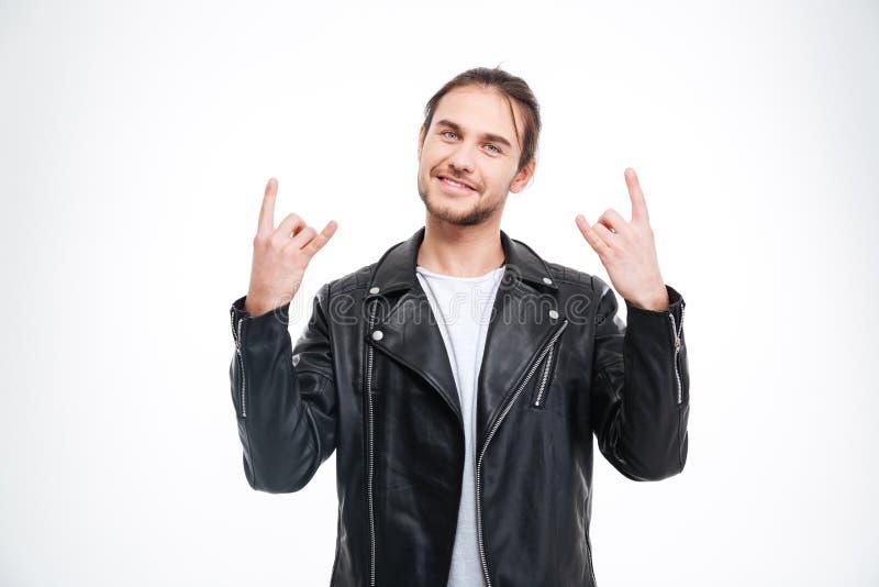 El hombre hermoso sonriente en la chaqueta de cuero negra que hace la roca gesticula fotos de archivo libres de regalías