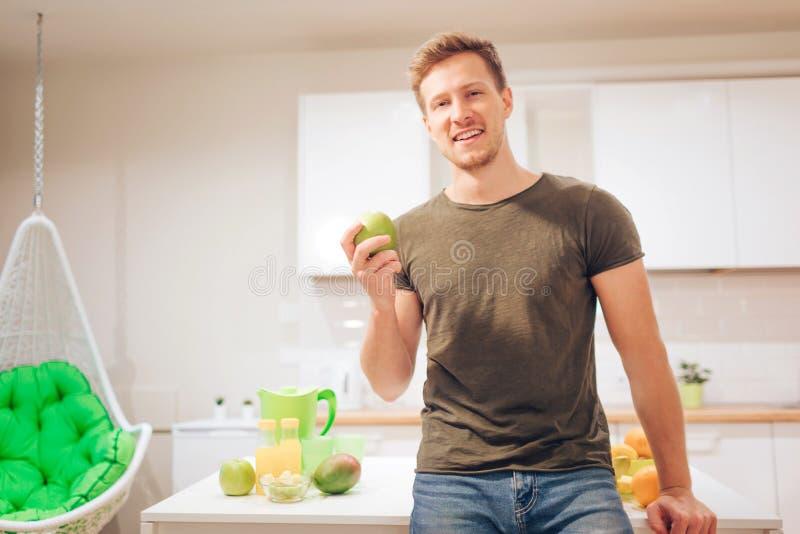 El hombre hermoso sonriente joven sostiene la manzana orgánica mientras que corta las frutas frescas en la cocina Consumición a l fotos de archivo