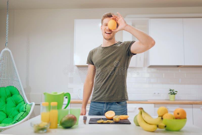 El hombre hermoso sonriente joven sostiene la naranja dulce delante de la cara mientras que cocina las frutas frescas en la cocin fotografía de archivo