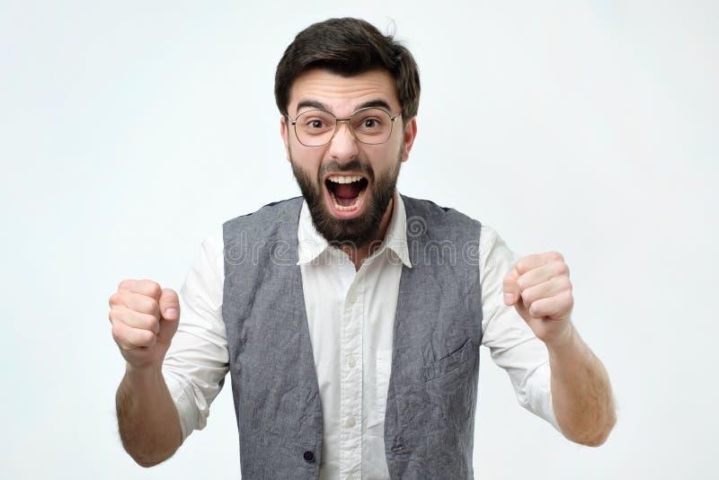El hombre hispánico maduro es feliz con su triunfo Él está llevando a cabo sus puños y grito wow imagen de archivo