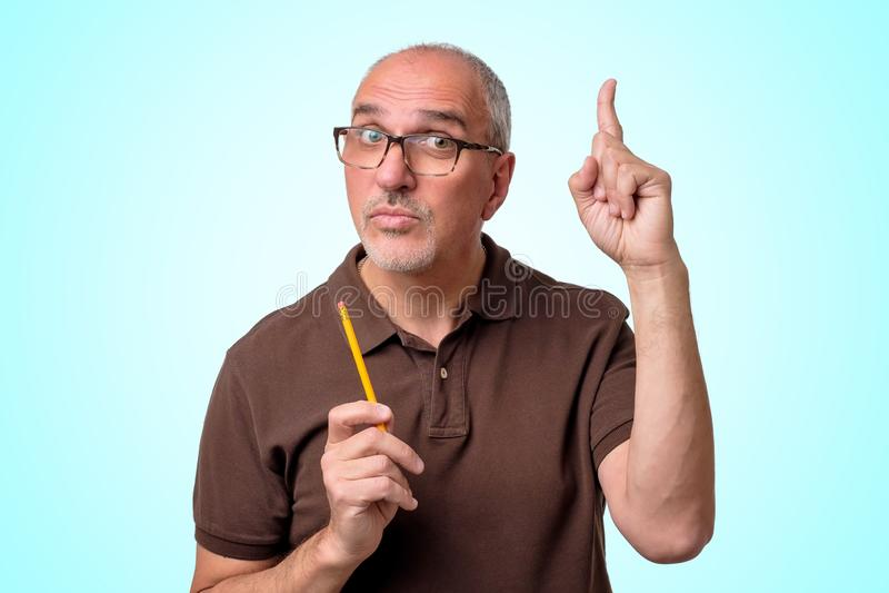 El hombre hispánico maduro tiene una buena idea que se coloca en fondo azul El profesor está sosteniendo el lápiz fotografía de archivo libre de regalías