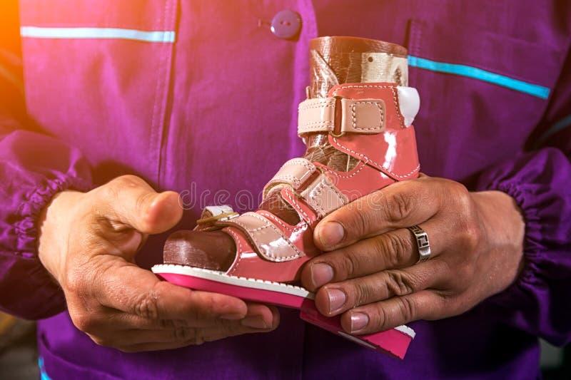 El hombre hizo los zapatos del ` s de los niños foto de archivo
