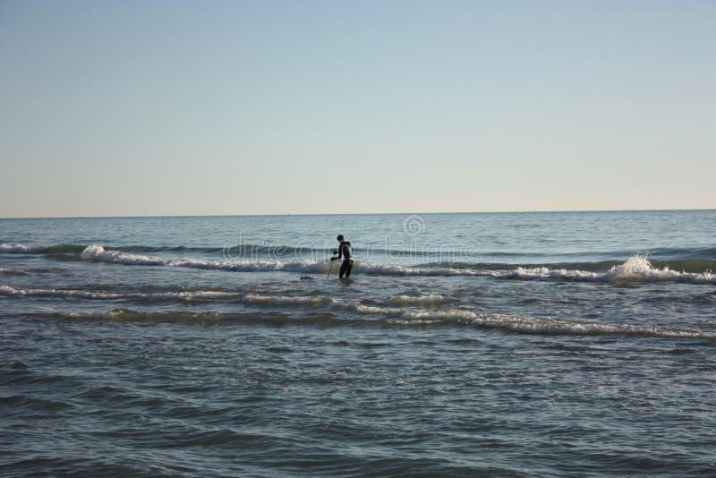 El hombre hundió en la pesca en mar y recoge tellines o las almejas u otros mariscos en un día de invierno fotos de archivo libres de regalías