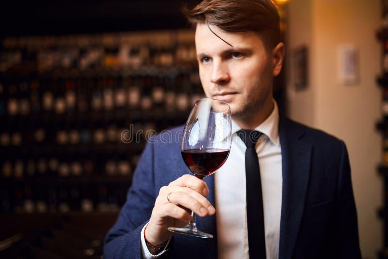 El hombre impresionante hermoso goza el beber del vino fotografía de archivo