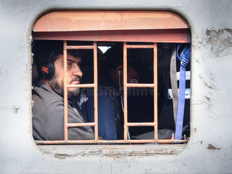 El hombre indio en auriculares se está sentando en tren, y está mirando a través de la ventana del tren en Sambhar Rajasth?n La I imagen de archivo