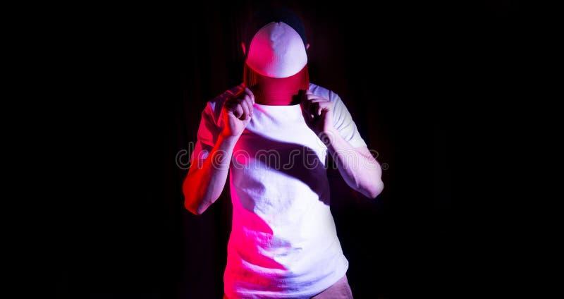 El hombre, individuo en la gorra de béisbol blanca, roja en blanco, en un fondo negro, mofa para arriba, espacio libre, presentac foto de archivo libre de regalías