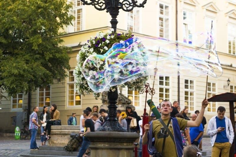 El hombre infla burbujas de jabón grandes en la plaza del mercado Wiev de la vida de ciudad imagenes de archivo