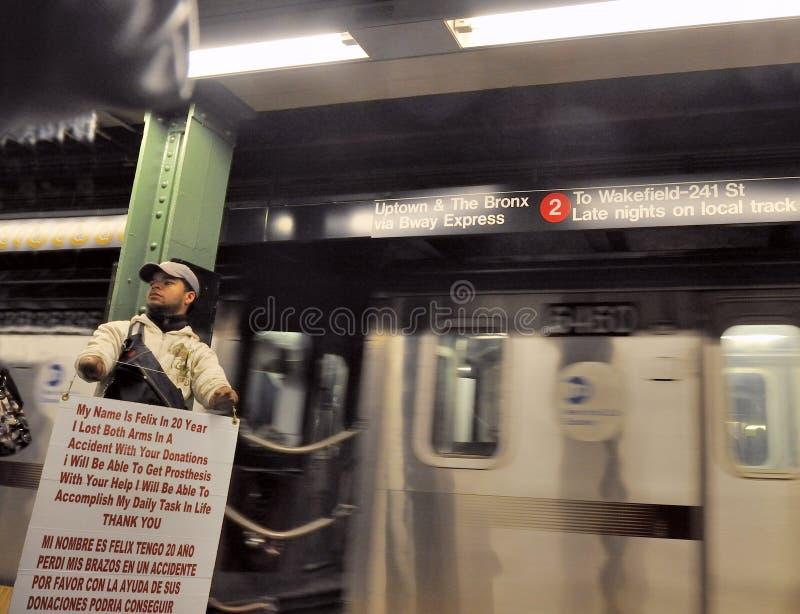 El hombre inhabilitado pide donaciones en la plataforma del subterráneo imágenes de archivo libres de regalías