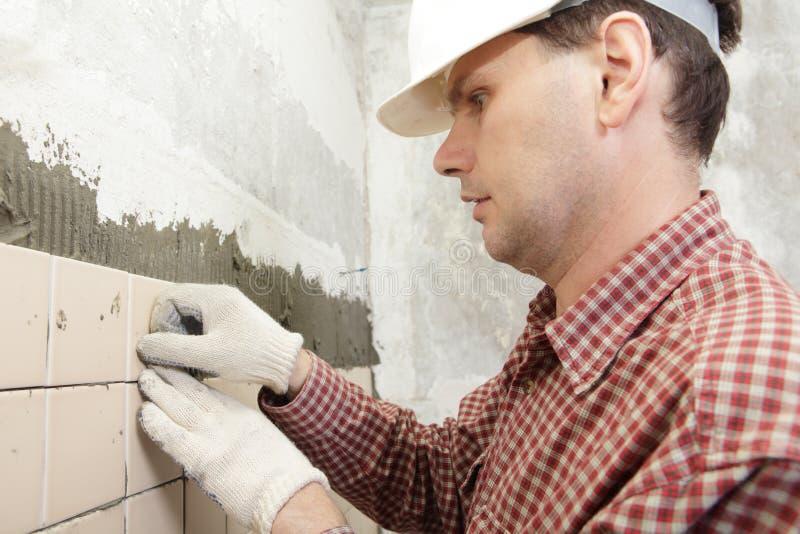 El hombre instala la baldosa cerámica foto de archivo