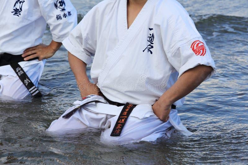 El hombre japonés del karate se sienta en actitud de la meditación en la playa foto de archivo libre de regalías