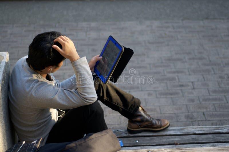 El hombre japonés está gozando de su tableta en un banco en el parque del este Higashi Yuenchi de Kobe en Japón foto de archivo libre de regalías