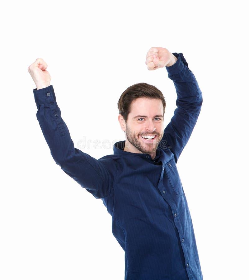 El hombre joven alegre con los brazos aumentó en la celebración imagen de archivo