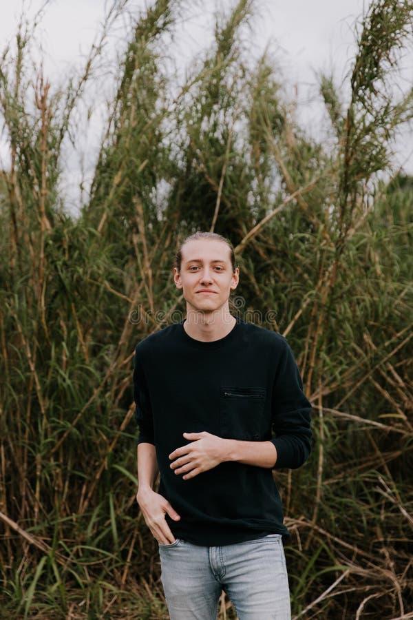 El hombre joven alto y hermoso con el pelo largo tiró detrás de modelado delante de exterior alto mismo de la hierba en natural imágenes de archivo libres de regalías