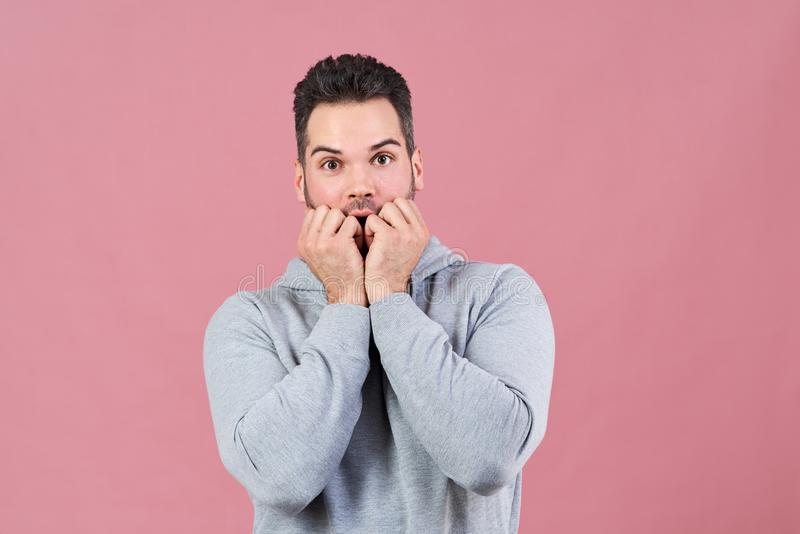 El hombre joven atractivo en miradas grises de la sudadera con capucha asustó en la cámara y presiona sus puños a su boca en una  fotos de archivo libres de regalías