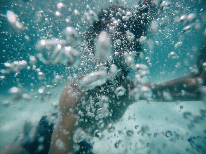 El hombre joven atractivo se sumergió en piscina con muchas burbujas fotos de archivo libres de regalías