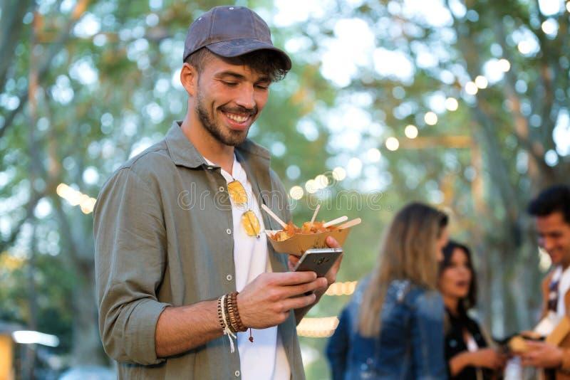 El hombre joven atractivo usando el teléfono móvil mientras que sostiene las patatas adentro come el mercado en la calle imagen de archivo libre de regalías