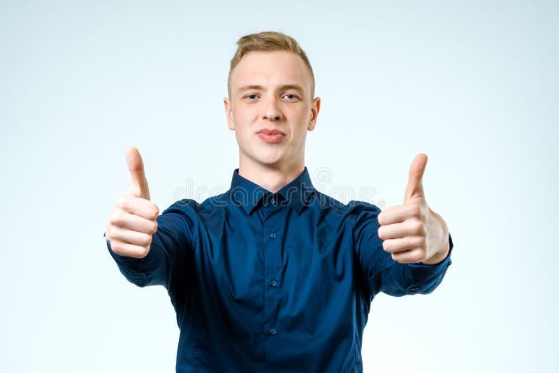 El hombre joven casual feliz que muestra los pulgares sube gesto imagen de archivo
