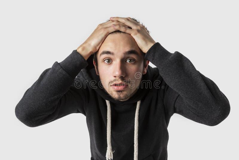 El hombre joven caucásico asustado está mirando en la cámara con las manos en su cabeza Concepto del error foto de archivo