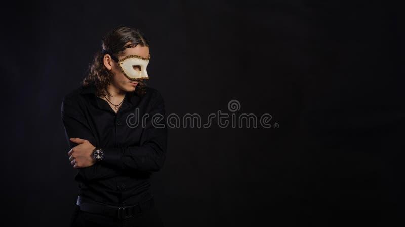 El hombre joven caucásico hermoso en una camisa negra con el mas blanco imagen de archivo libre de regalías