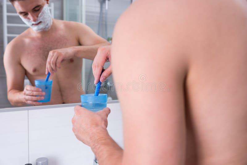 El hombre joven con afeitar espuma en sus mejillas lava su maquinilla de afeitar en th foto de archivo libre de regalías