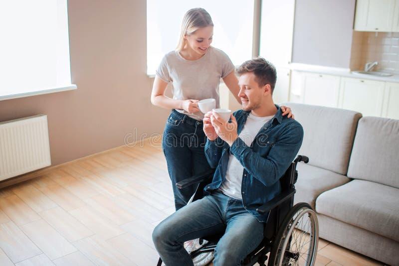 El hombre joven con incapacidad se sienta en la silla de ruedas Persona con necesidades especiales Sostener la taza de caf? as? c fotos de archivo libres de regalías