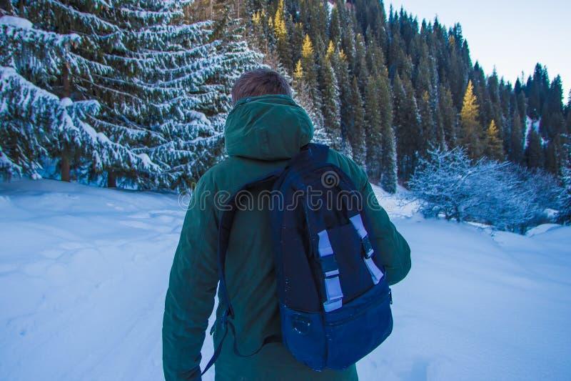 El hombre joven con la mochila está caminando en montañas del invierno La parte posterior compite fotografía de archivo