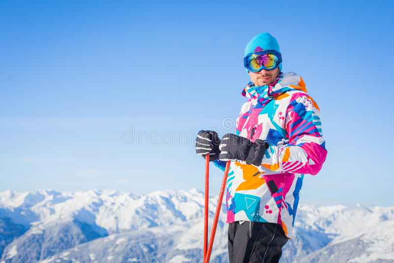 El hombre joven con los esquís y un esquí desgastan foto de archivo