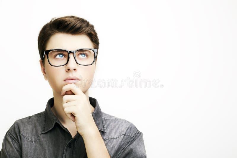 El hombre joven con los vidrios está pensando en el fondo blanco foto de archivo