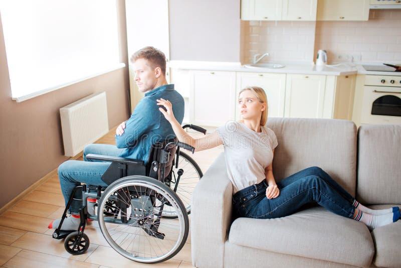 El hombre joven con necesidades especiales se sienta en la silla de ruedas de nuevo a la parte posterior con la mujer Ella toca s imagen de archivo