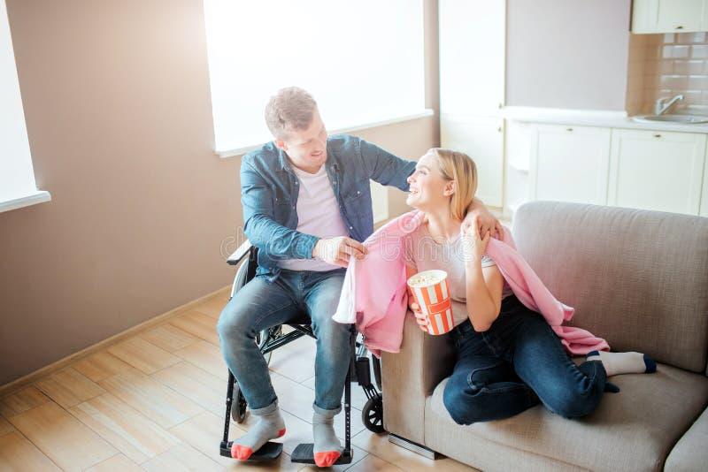 El hombre joven con necesidades especiales toma el cuidado de la novia ?l se sienta en la silla de ruedas y hacia fuera combinado foto de archivo libre de regalías
