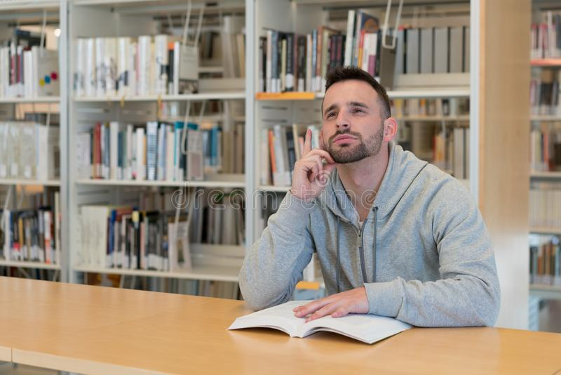 El hombre joven con su finger aumentó el alto pensamiento en respuestas posibles con un libro en la tabla en la biblioteca imagen de archivo libre de regalías