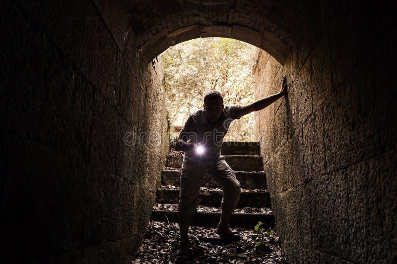El hombre joven con una linterna entra en el túnel de piedra imagen de archivo libre de regalías