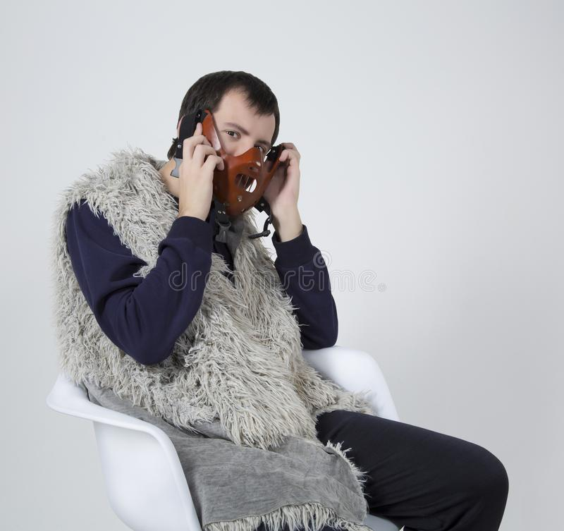 El hombre joven con una máscara en su cara se sienta en una silla blanca imágenes de archivo libres de regalías
