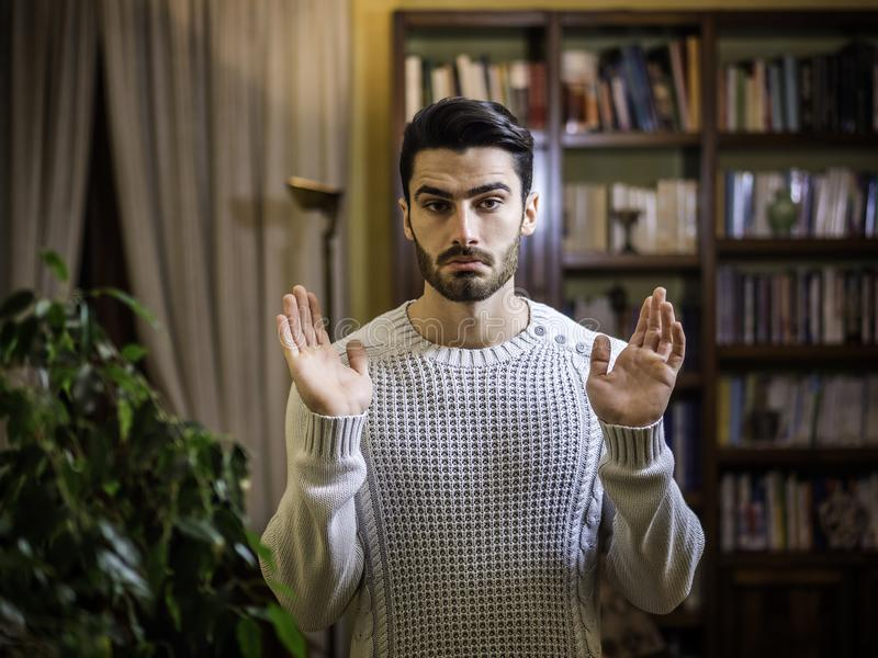 El hombre joven confuso o dudoso que encoge con las palmas se abre imagen de archivo