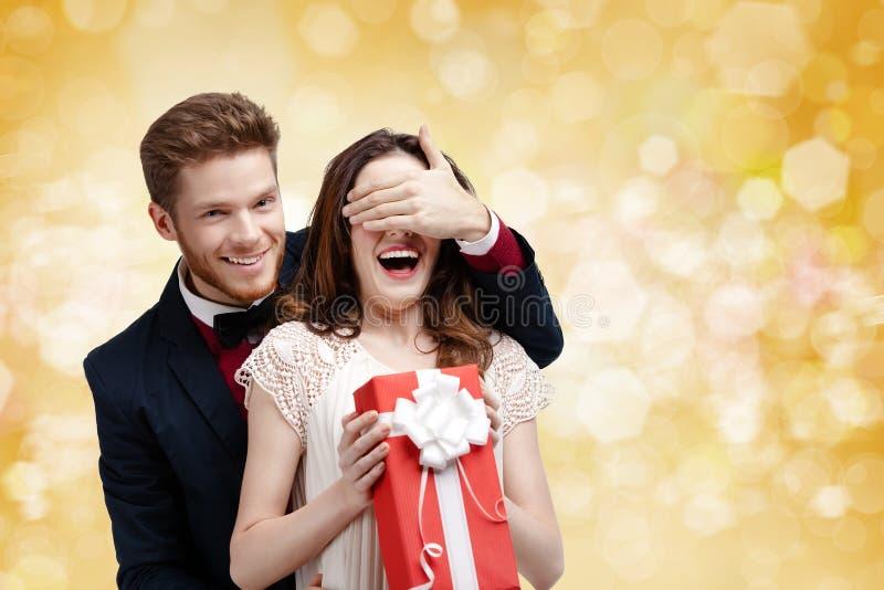 El hombre joven cubre ojos de su novia fotografía de archivo