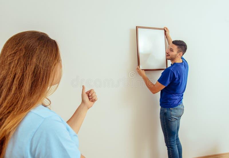 El hombre joven cuelga la imagen del arte en la pared en casa imagen de archivo libre de regalías