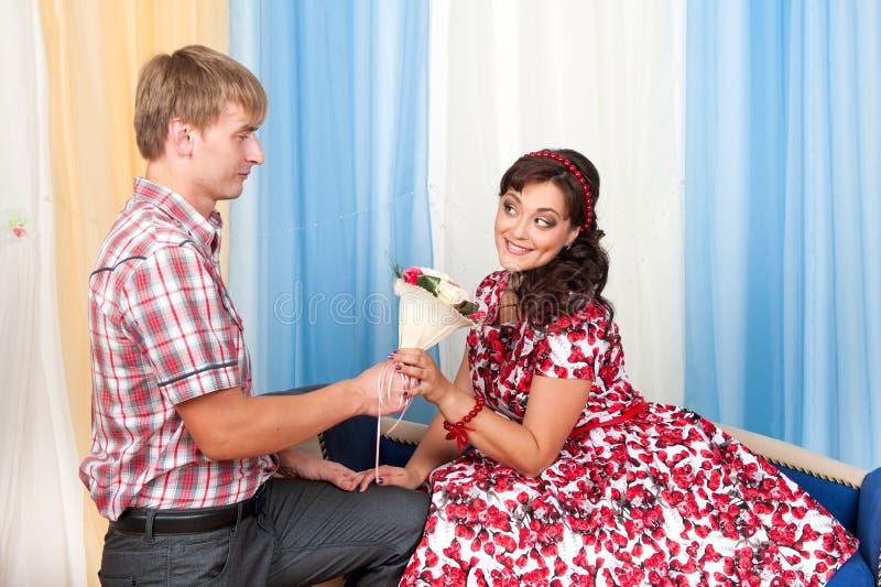 El hombre joven da a mujer hermosa las flores imagenes de archivo