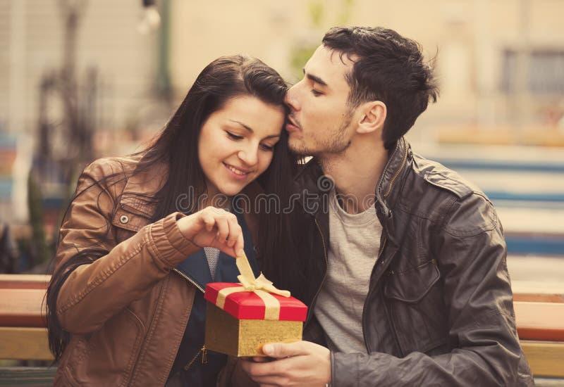 El hombre joven da un regalo a una chica joven en el café y ellos foto de archivo