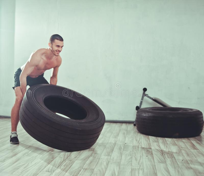 El hombre joven de los deportes aumenta una rueda grande del peso fotografía de archivo